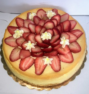 Creamy vanilla cheesecake decorated with sliced strawberry design and vanilla buttercream frosting flowers with graham cracker crust. $46, serving 12 people.